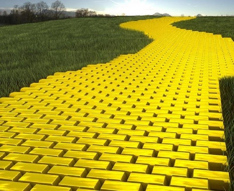 There is path made up of gold bars placed in a sequence like floor tiles, with grass on both sides