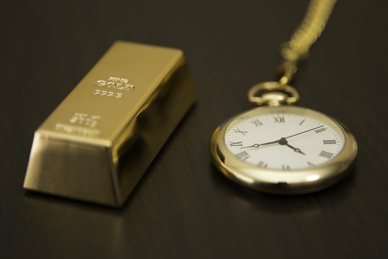 Gold bar placed next to watch