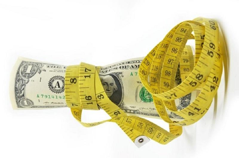 Images shows a yellow measuring tape wrapping around the dollars