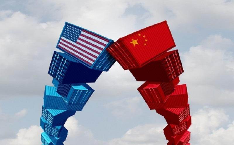Image shows blue stack of blocks with American Flag printed on the top most and another stack of red blocks with Chinese flag printed on the top most