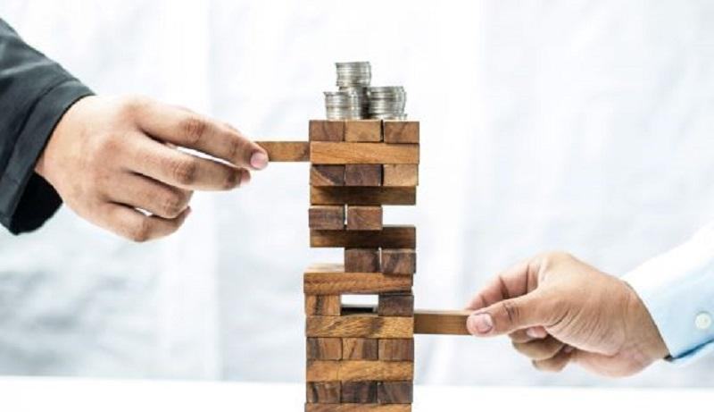Images shows two people playing the games Jenga - wooden stacks game with silver coins on the top