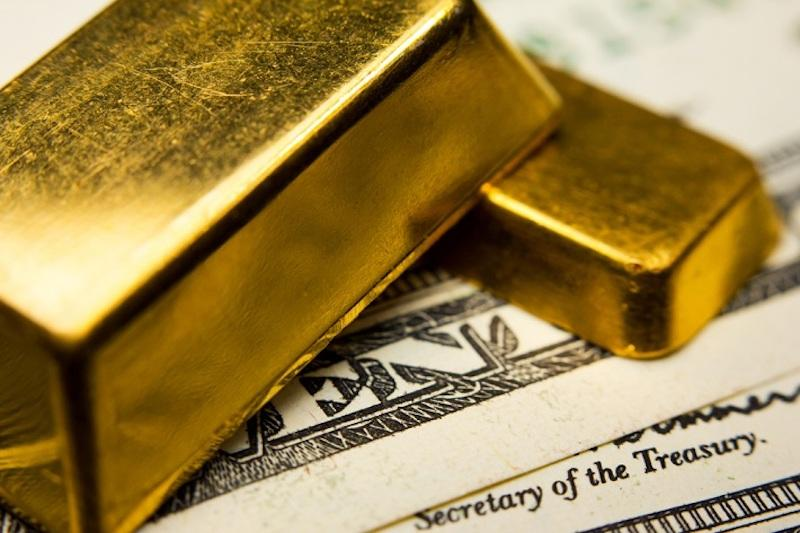 Gold bars placed on top of US Currency