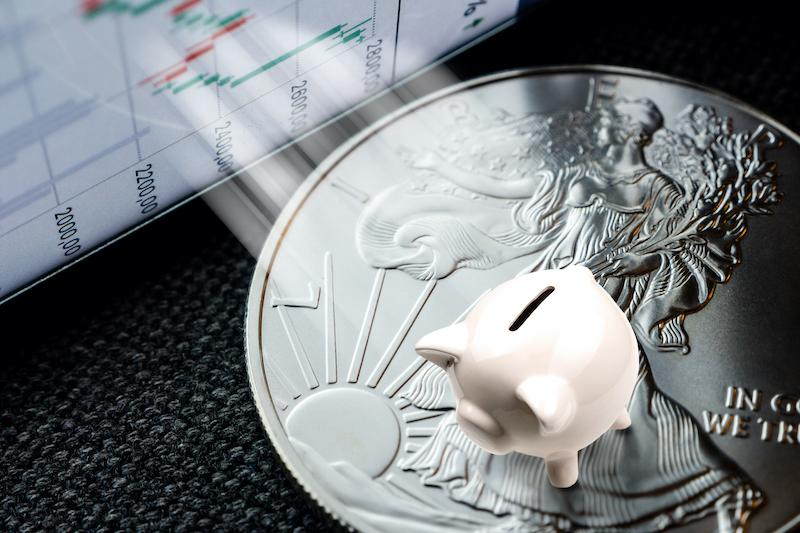 Small piggy bank placed on top of silver coin