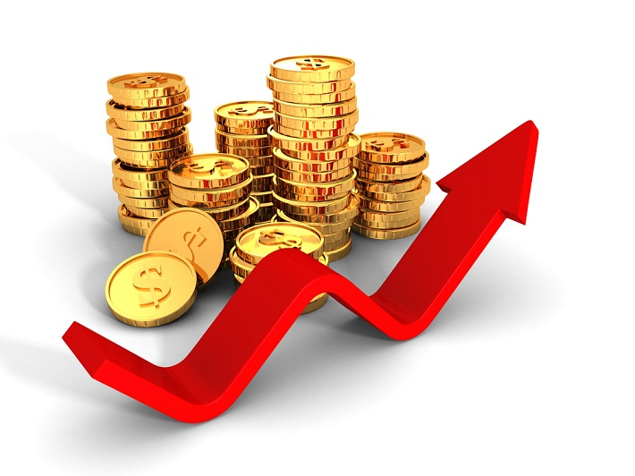 Stacked gold coins behind a fluctuating graph