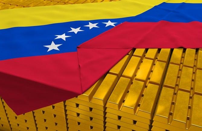 Image of Venezuelan flag drapped over stacks of gold bars