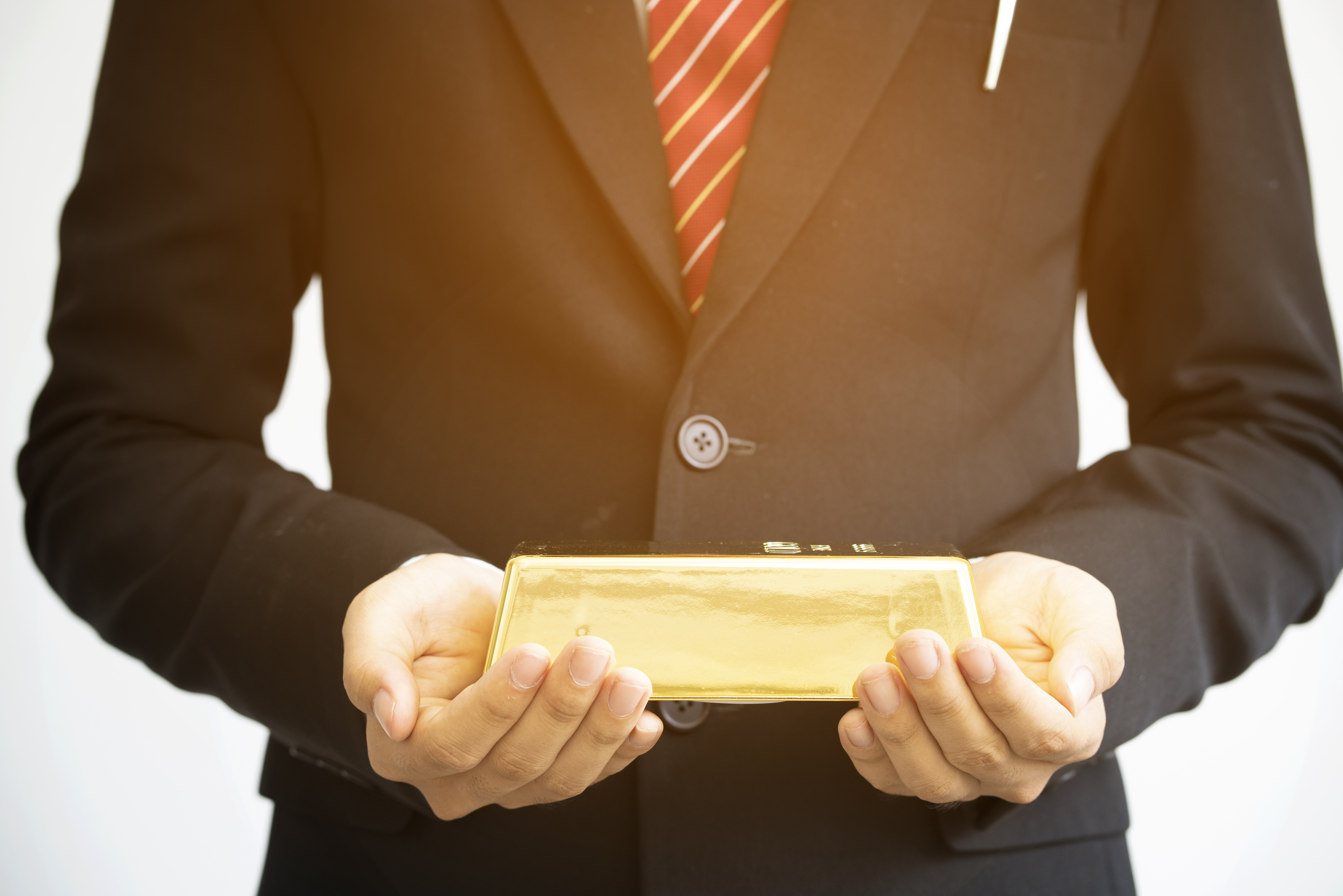 Man in black suit holding a gold bar