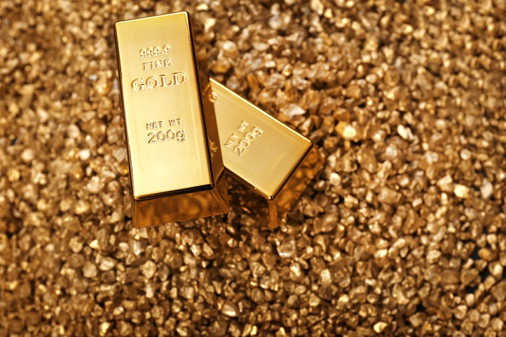 Image of gold bars sitting on a pile of small gold nuggets