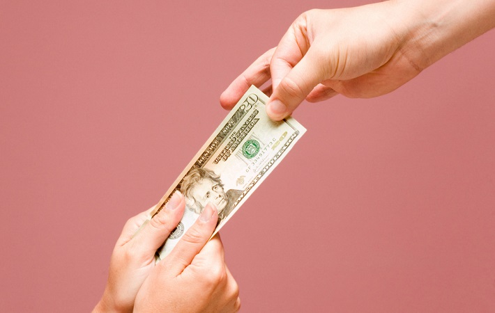 Image showing one hand giving away the dollar bill and other two hands taking that bill