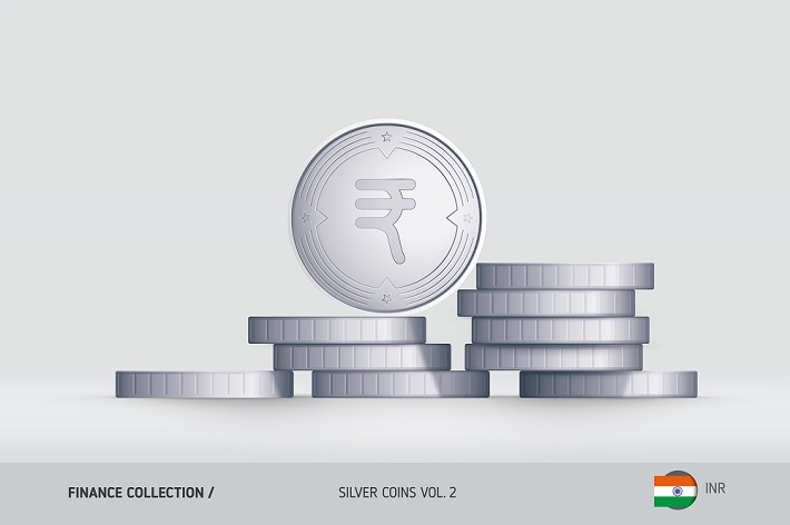 Silver coins stacked randomly with one standing coin on the top