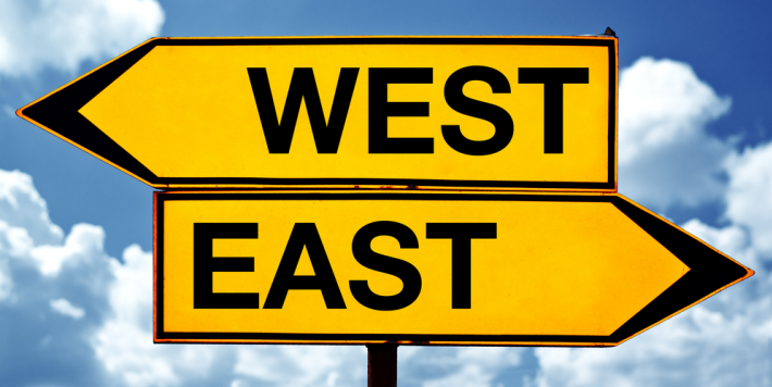 two street signs, one says east, one says west, pointing in opposite directions