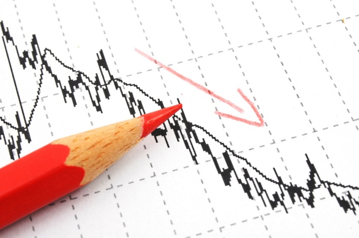 Partial image of a red pencil sitting on a downward trending graph with a red arrow pointing down.