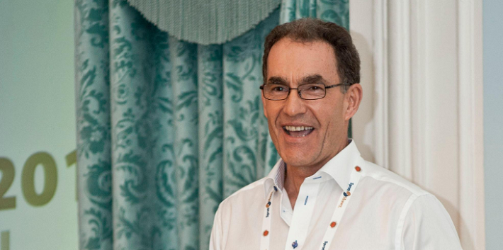 Andrew Maguire in white shirt standing in front of bi-colored curtains
