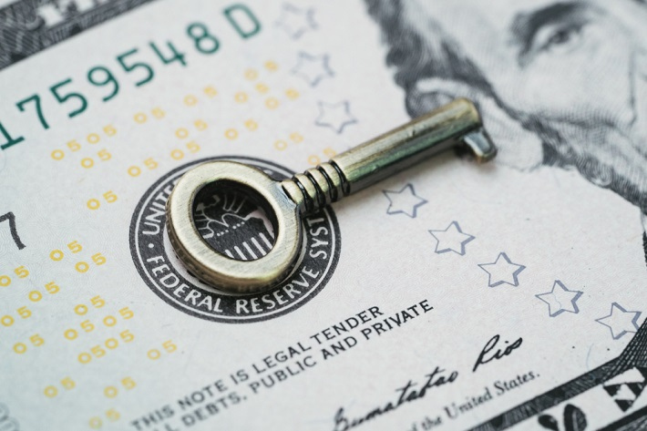 Silver key placed on the paper money