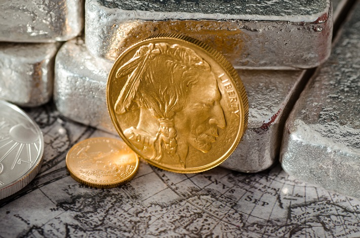 A gold buffalo coin standing against silver bars