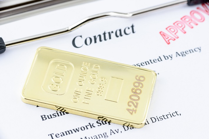 Gold bar resting on an approved contract paper