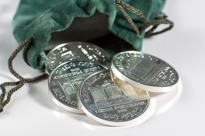 Image of green pouch with silver coins on a table