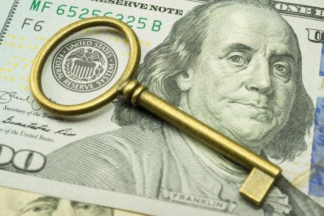 Old fashioned gold key sitting on a US dollar.