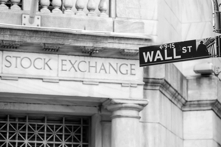 Partial image of the outside of the stock exchange building with a street sign that says Wall Street
