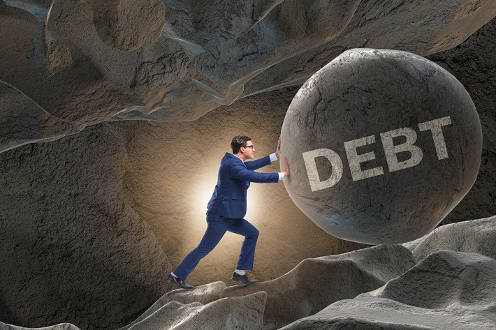 A man pushing the rock named debt uphill