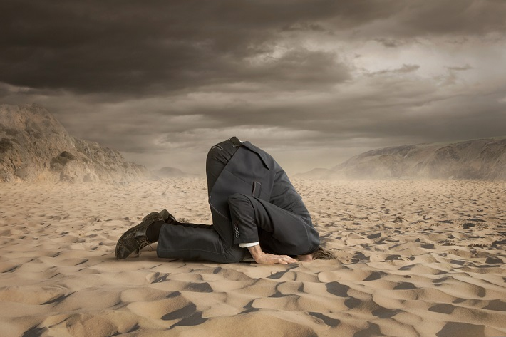 Image of business man on his knees with his head burried in the sand.