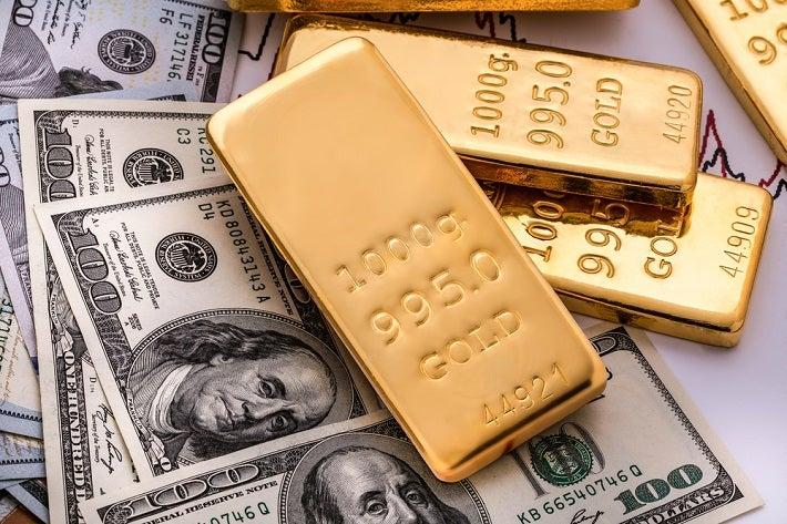 Gold bars sitting on US paper money