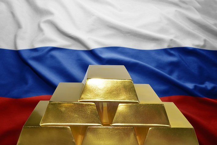 Stack of gold bars in front of a Russian flag.