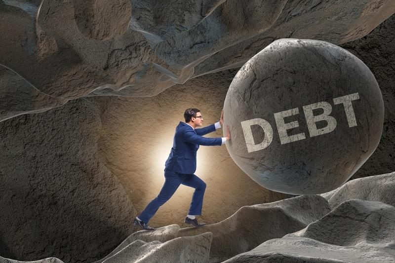 Image shows a man pushing big boulder with debt written on it